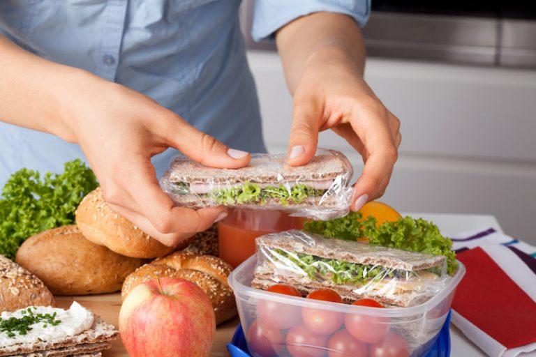 Imagen de una persona colocando comida en un contenedor