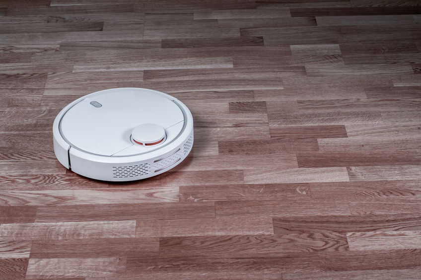 White robotic vacuum cleaner runs on laminate floor. Robot controlled by voice commands for direct cleaning. Modern smart appliance for cleaning house
