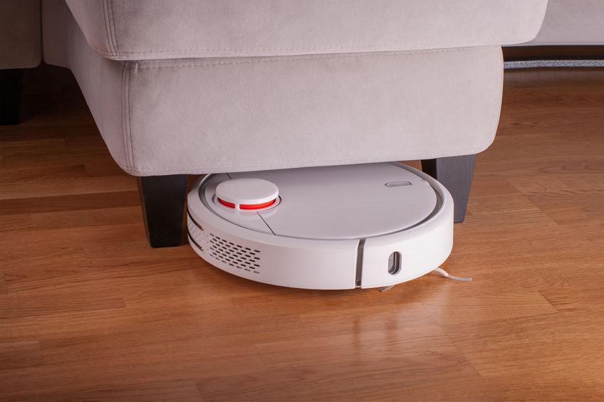 Robot vacuum cleaner runs under sofa in room